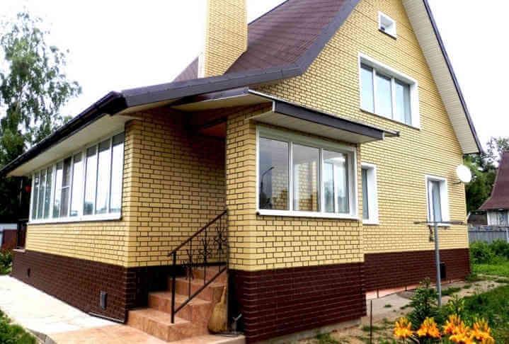 Стены частного дома облицованы цокольным сайдингом под кирпич